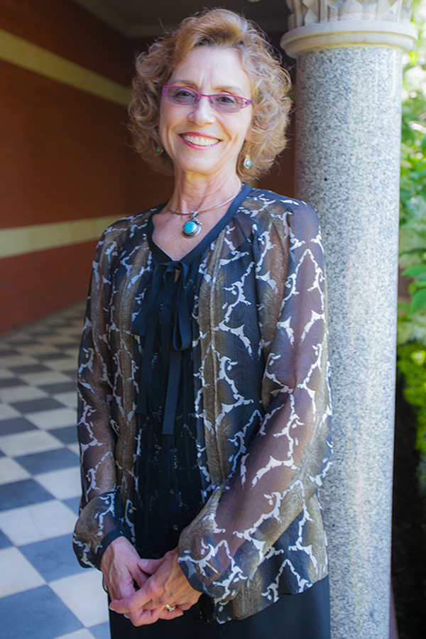 Dr Carol Erting standing outside by a column, gauzy gray top, pink glasses, chin length curly brown hair