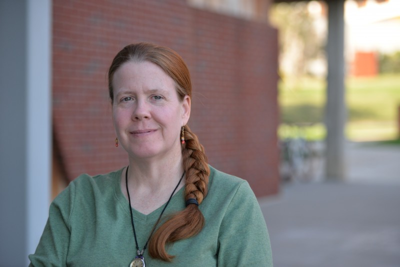 Photo of Dr. Barbara Stock. Philosophy Program Coordinator.  Dr. Stock has long red hair which is pulled back; she is wearing a short sleeved green t-shirt. and is standing outside of the SAC against a red brick wall.