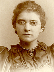 Agatha Tiegal Hanson in her class photo from 1893. The image has a grayish tone.  She's wearing a dark dress and a necklace. Her glasses have small roundish frames, and her hair is pulled back