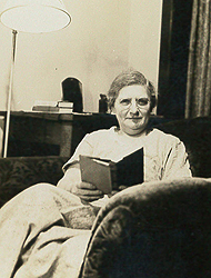 Agatha Tiegal Hanson, sitting in a comfortable chair, with a book in her hand. She is looking at the camera. A lamp is in the background.