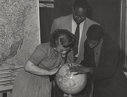 Andrew Foster standing over two students peering over a globe.