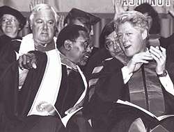 Glenn Anderson and President Bill Clinton in graduation robes, chatting. Anderon is pointing outward, toward the students