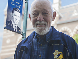 Jack Gannon standing near the light pole banner that bears his 1959 class photo. He's wearing his '59 class jacket and is smiling, with a bearded face.