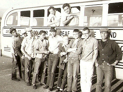 Arizona School for the Deaf and Blind. Two boys leaning out of bus windows, while seven boys lean against the bus.