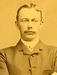Olof Hanson in his school picture from 1886. The image appears to have an orange tone. Hanson is wearing a suit and is sporting a mustache.