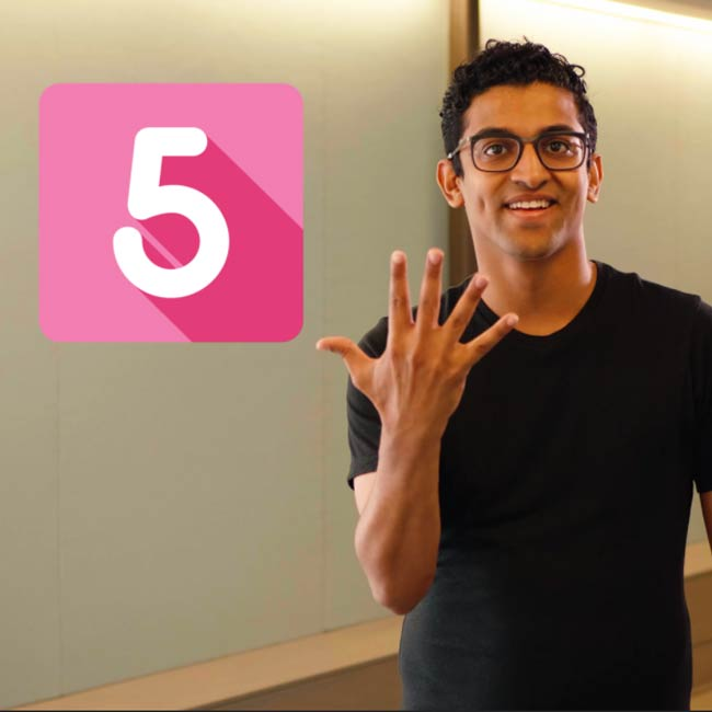 "Hispanic man signs ""Five"" with pink block and white number of 5 icon"
