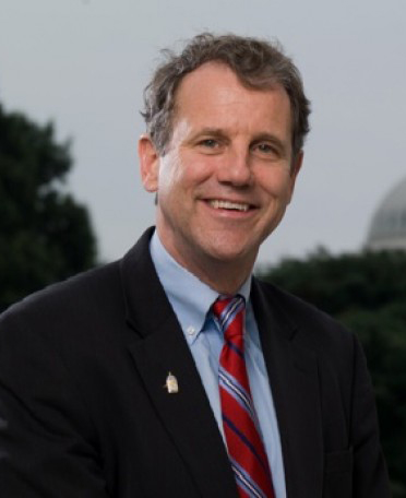 Senator Sherrod Brown (D-Ohio) sits outside near the Capital building, with a dark suit, blue shirt and red, tie with blue and white stripes.