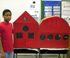 Image: A KDES student with red model building in a classroom