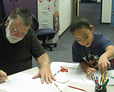 Image: KDES student Alyssa Biega works alongside Chuck Baird on a De'VIA  artwork project.