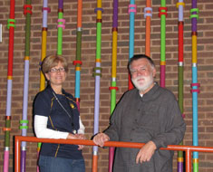 Image: KDES principal Nancy Berrigan stands with Chuck Baird in front of the art installation Baird created which will be mounted on the walls of the KDES auditorium.