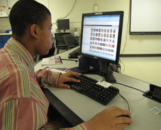 Image: Marcus Pointer, sports copy editor for the KDES yearbook, reviews captions for basketball photos.