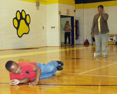 "Image: Student Keonte Marshall demonstrates ""Stop, Drop, and Roll"" while Patricia Everett from the D.C. Fire Department observes."