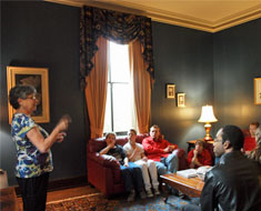 Image: First Lady Vicki Hurwitz entertains the cast with the history of House One. (Photo: Susan Flanigan)
