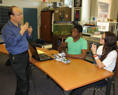 Image: Teacher Mark Tao and students Daimere Phillips and Margaret Hangstorfer discuss how to solve a technical problem with their robot.