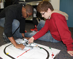 Image: Students Emmanuel Njoku and Matt Thompson test out their LEGO robot on a game board. (All photos: Susan Flanigan)