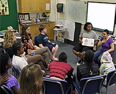 "Image: Alicia Johnson and Chelsea Lee (MSSD '12) read a book about baseball hero Leroy Robert ""Satchel"" Paige with the students in the grades three, four, and five language arts class."