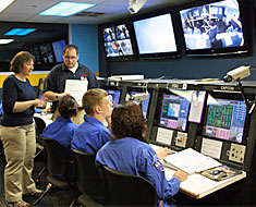 Image: The mission control center crew receives a basic overview of the simulation and hints on reading mission reference materials. The deaf crews are able to communicate with the commander, pilot, mission specialist, and flight engineer through the TV screens.