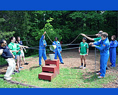 Image: The team attempts to complete a challenge at area 51 by using ropes to move a bucket with green balls to another bucket without touching the bucket. The success of the activity depends on teamwork, trust, communication, decision making, self-confidence, cooperation, and leadership skills.