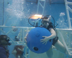 "Image: Sierra Saylor moves a 100-lb iron ball as she experiences underwater astronaut training. ""Due to the neutral buoyancy in water, it does not feel that heavy,"" she said."