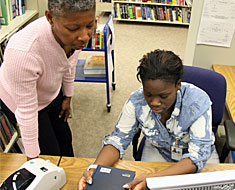 Image: Vera Clyburn, Section Head, Science, Technology, and Medicine, reviews with intern Serena Dorch the procedures for labeling books.