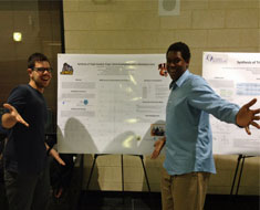 "Image: David Bruno (left) and JMU student Brenden Wimbish stand in front of their poster presentation on ""Synthesis of Triple-Headed, Single-Tailed Amphiphiles with a Mesitylene Core."" (Photo: Courtesy of David Bruno)"