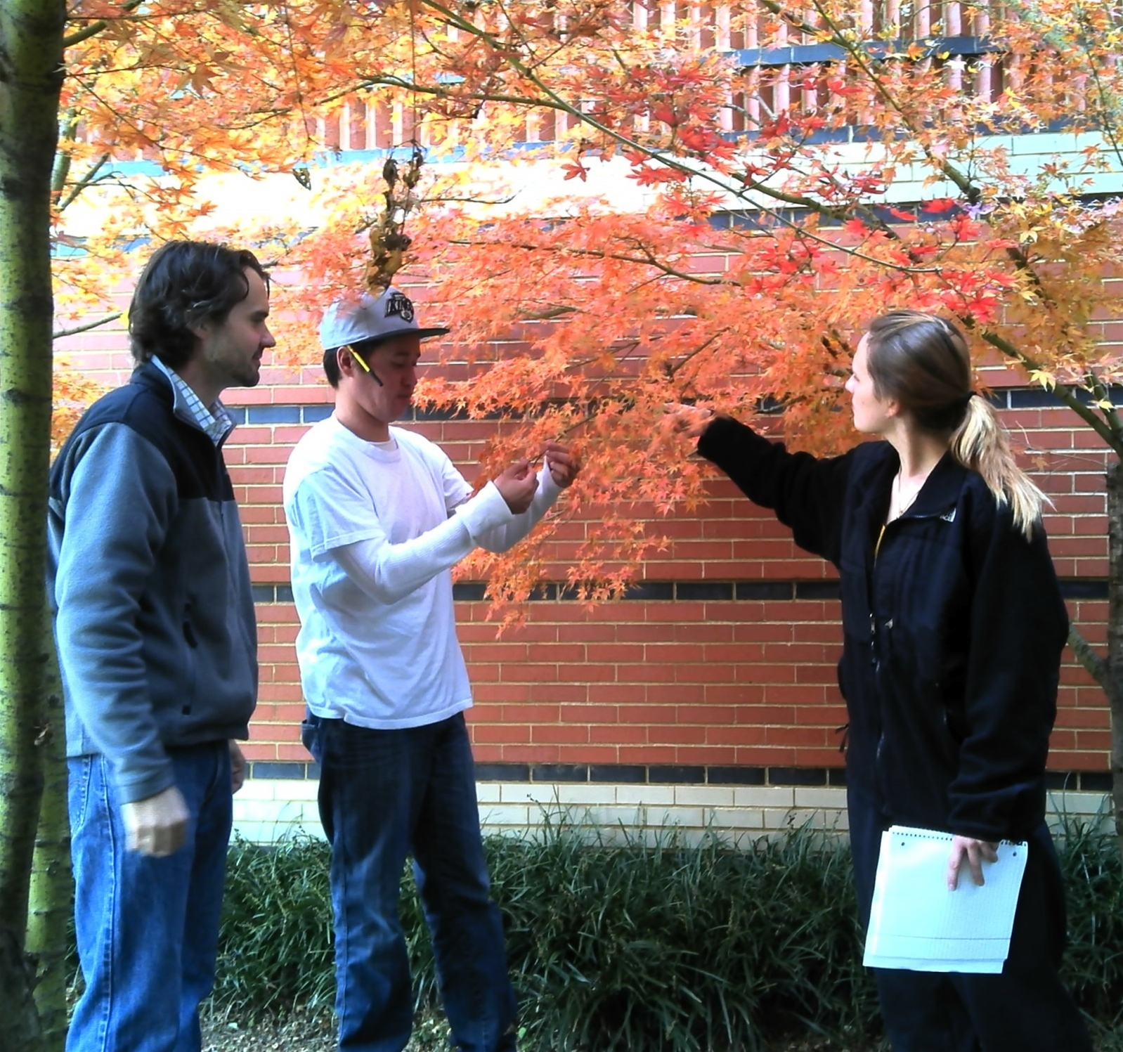 Dr. Daniel Lundberg, John Cha (Chemistry major), and Sheena O'Donnell (Biology major/Chemistry minor) outside the Jordan Student Academic Center collecting a sample.