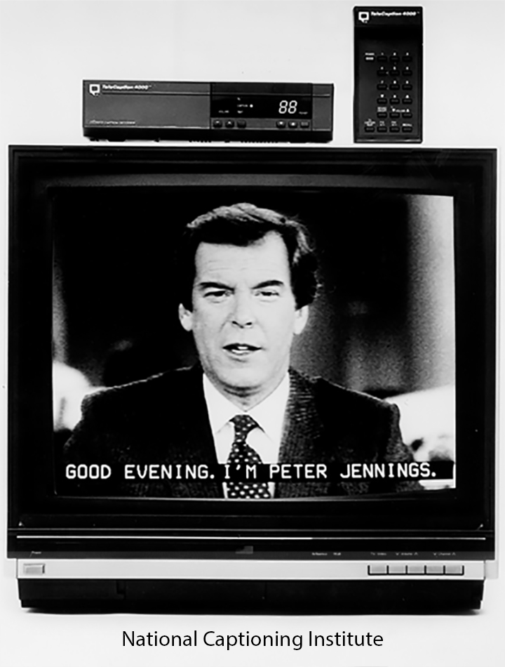 Photo of a captioning decoder on top of a television as Peter Jennings of ABC News is depicted in the TV monitor.
