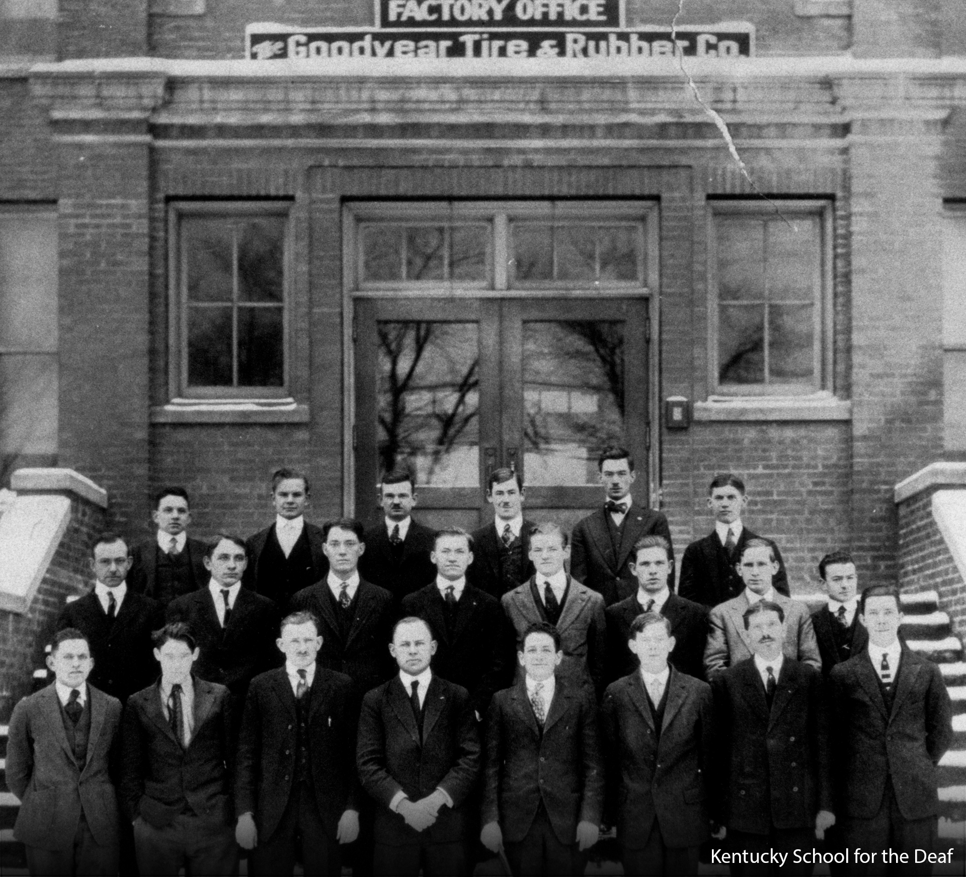 Three rows of KSD Alumni men in their dark suits pose on the factory steps.