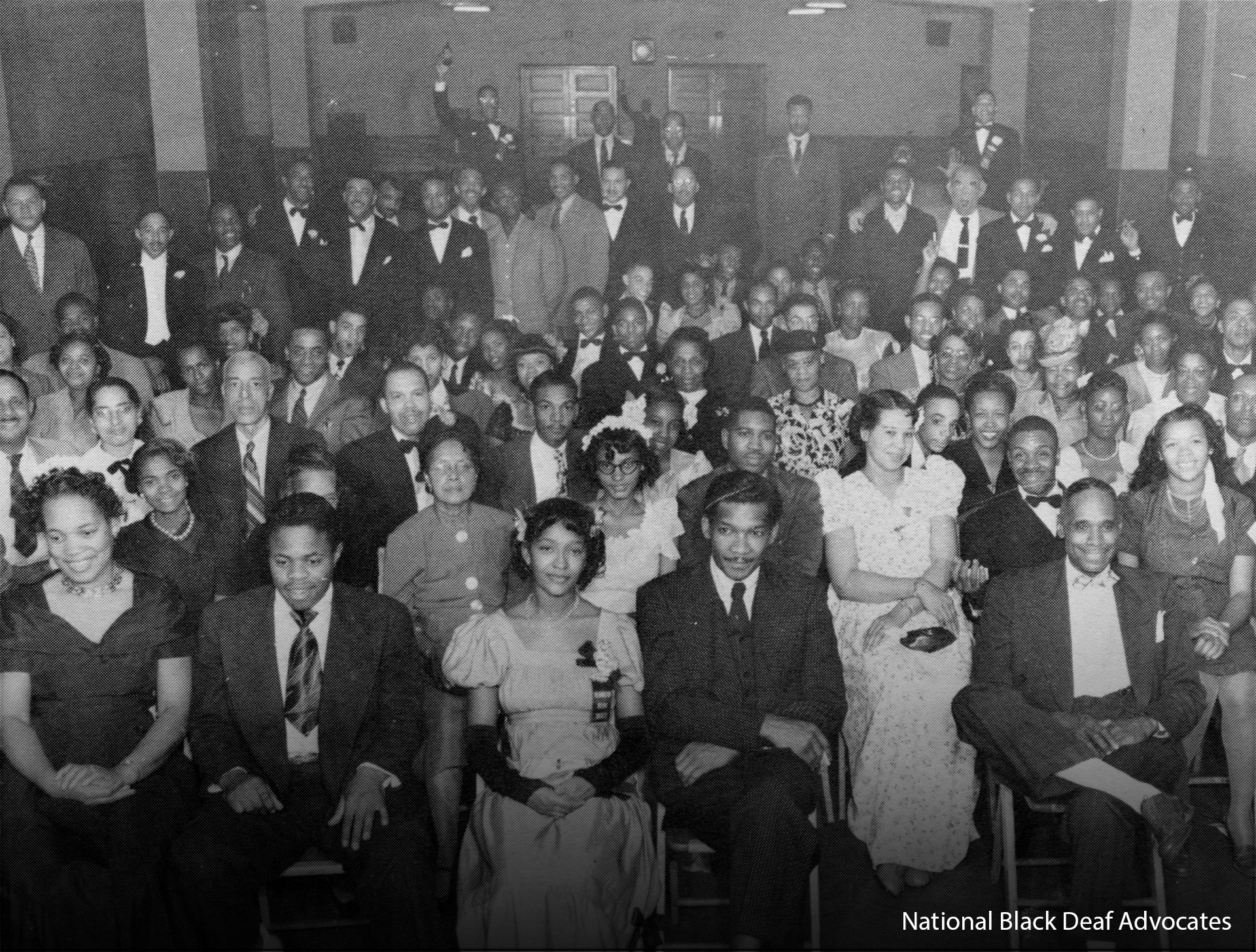 Approximately 100 to 125 Black Deaf people smile pose for a group photo.