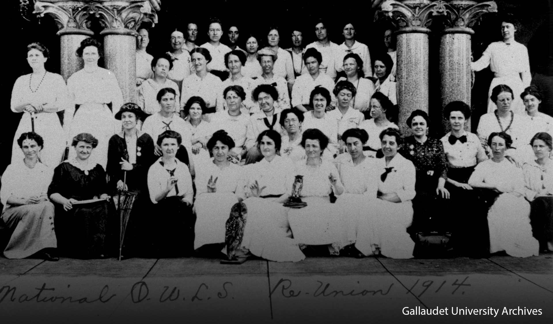 "Approximately 40 women posing at the steps of Chapel Hall with a statue of an owl. Four members in the front row fingerspell the word ""O.W.L.S."""