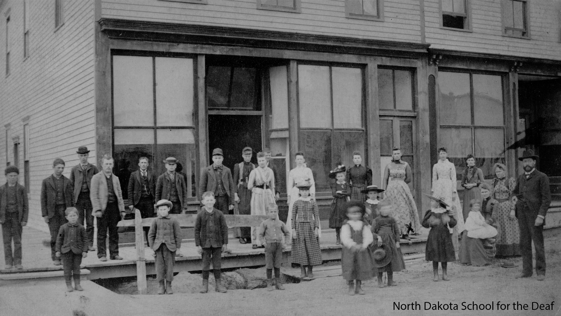 Deaf people standing in front of the North Dakota School for the Deaf