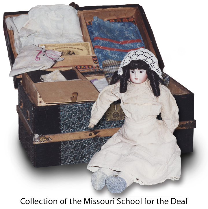Doll's clothing trunk with a doll in front of it. Doll made in 1905 which belonged to Mrs. Ivy Steward Shipman, Missouri School for the Deaf.