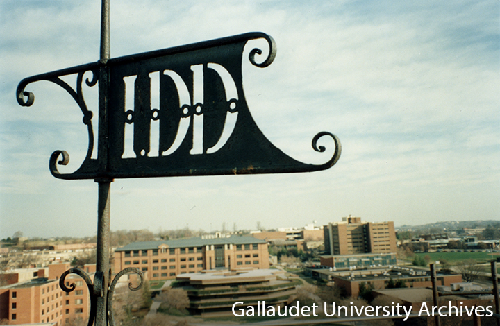 "Close up photo of ""IDD"" weathervane on top of Chapel Hall overlooking over the west side of Gallaudet campus."