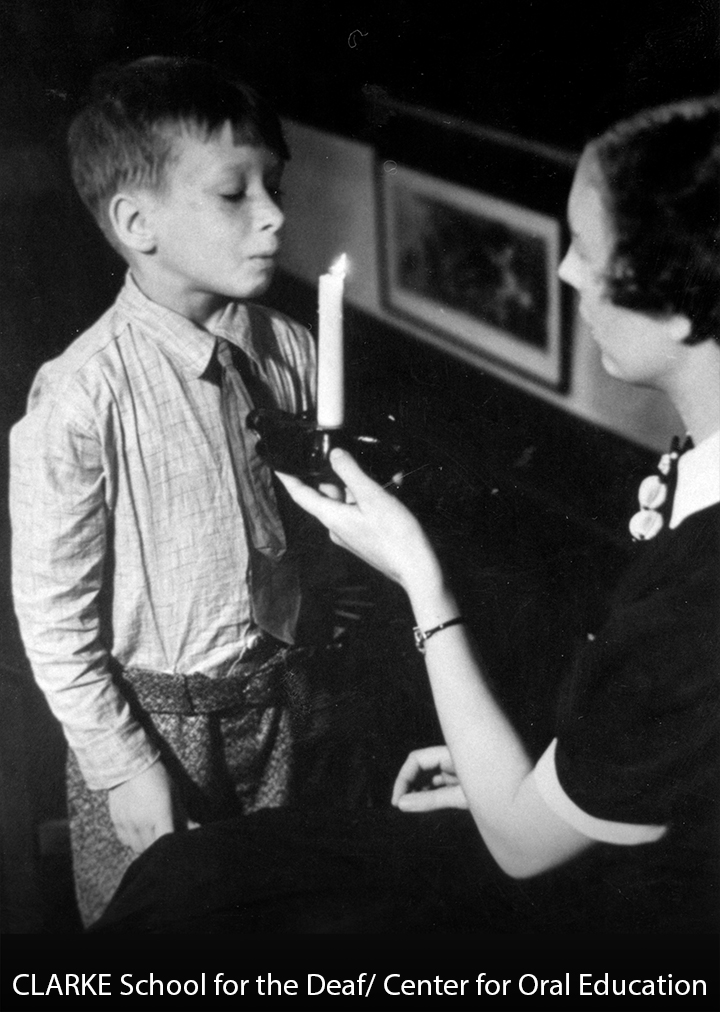 The female teacher holds the candle at the male child while he stands in the front of the candle.