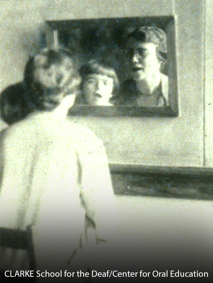 Teacher practicing speech with a female pupil in front of a mirror.