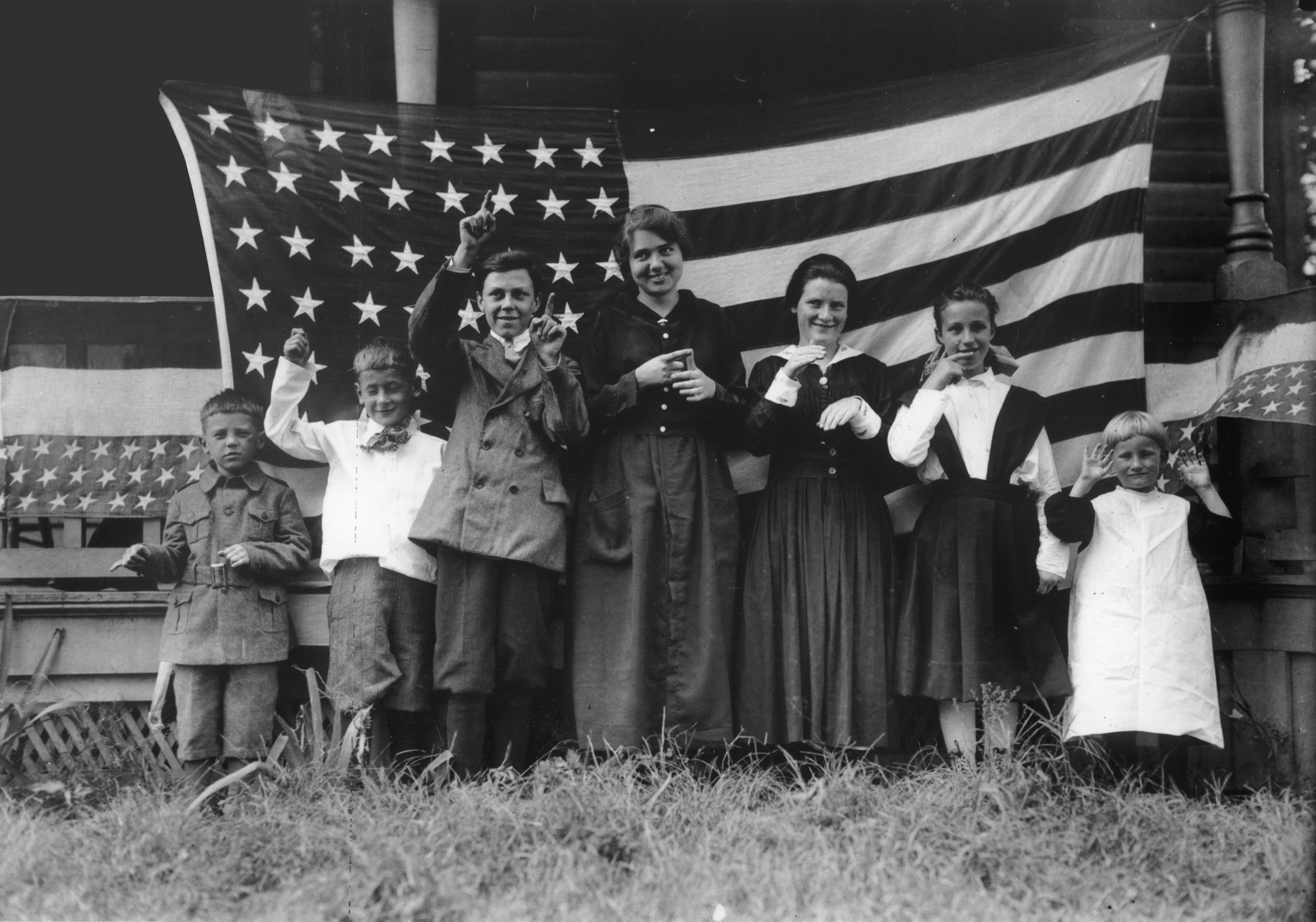 Woman in white dress with left first raised up while on the ri ght hand leaning on the U.S. Flag