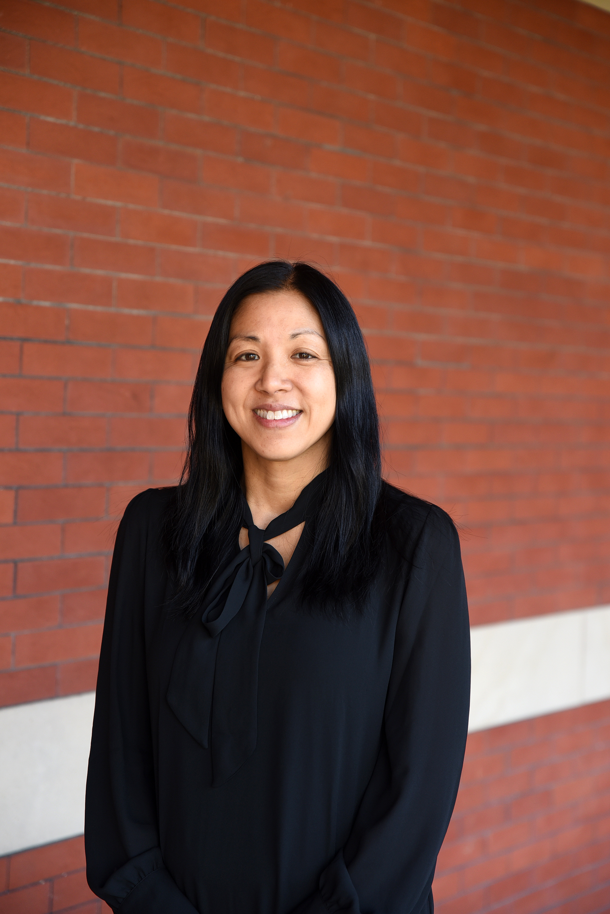 A picture of a smiling asian woman with a black suit standing in the front of a red brick wall