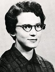 Alice Lougee Hagemeyer's class picture from 1957. It's a black and white photo. She's wearing a dark color dress and glasses.