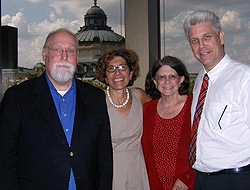 Hagemeyer, wearing a red outfit is posing with two men and one woman, all dressed professionally; described below. They are standing near a window and a dome shaped building is behind them.