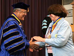 Alice Hagemeyer shakes Gallaudet's former president Robert Davilla's hand. He's wearing his formal Gallaudet robes. She is wearing a sweater, pants and a light blue jacket.