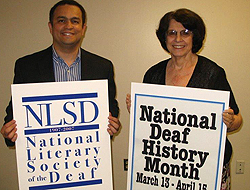 "Richardo Lopez in a jacket and shirt holds up a sign that says, ""NLSD"" National Literary Society of the Deaf."" Alice Hagemeyer stands next to him with a black blouse, holding a sign that says, ""National Deaf History Month, March 13-April 15 (date not clear)"