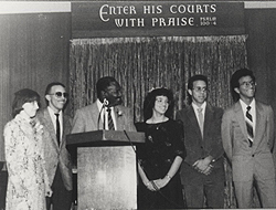 Foster at the church podium with others behind him
