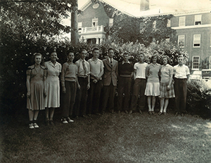 Bernard Bragg's class at American Scool for the Deaf in 1943. They are standing outside in front of a building, on a grassy area with trees and bushes behind them.