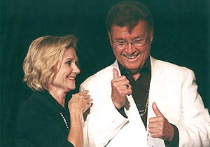 Bobbi Scoggins in a dark outfit stands next to Bernard Bragg, who's wearing a white suit jacket and is signing something.