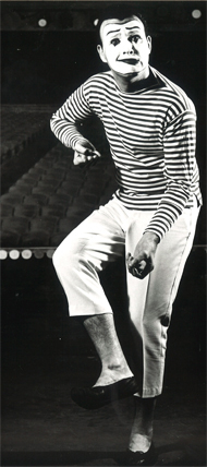 Bernard Bragg in striped shirt, white pants that mimes typically wear. His face has white makeup and made up eyebrows, eyes and lips, as mimes typically do. He's doing a mime pose, with a smirk like expression