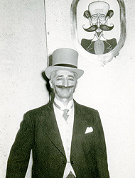 David Peikoff wearing a tux with a tie and vest, with a hankerchief in the left chest pocket. He has a top hat and a large mustache, which appears to be fake.