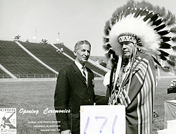 David Peikoff on a football field, in a suit and tie, standign next to a Native American Chief with a large headress and native garb. A square with the number 171 is below them and there is some printed text next to that. Text is not readily visible.