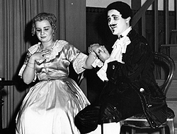 Gertrude Galloway and Bernard Bragg in period clothing, on stage, acting.