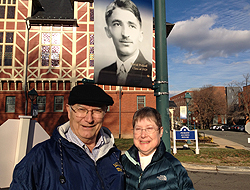 Pauline and David Peikoff's daughter Joyce poses in front of Peifkoff's lightpole banner with her husband Dr. Richard Meisegeier.