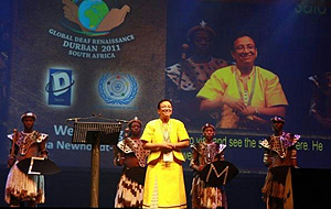 Wilma Newhoudt-Druchen on stage with four South Africans in traditional garb behind her, a large screen with a logo and live video focused on her is in the background.